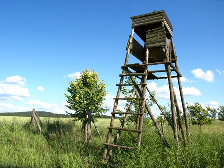 Old wooden deer stand in fields photo
