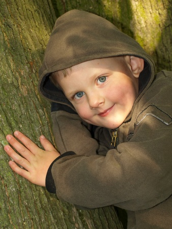 causasian: A happy hooded boy in wood Stock Photo