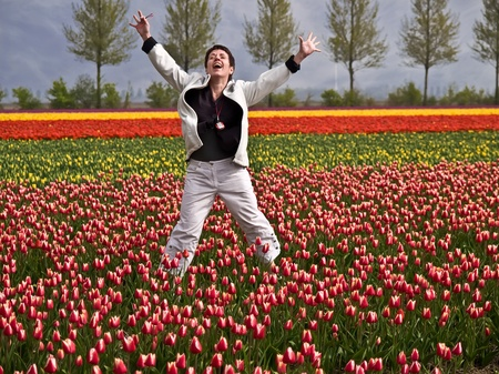 Happy woman jumping in a tulip field photo