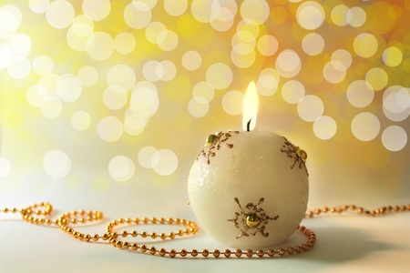 Lit christmas candle with abstract bokeh background, golden color