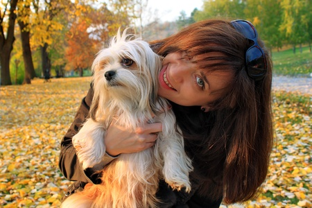 Young woman playing with her lhasa apso dog in a beautiful park covered with fallen leaves photo