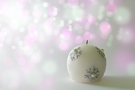 Christmas candle on a subtile colored bokeh background photo