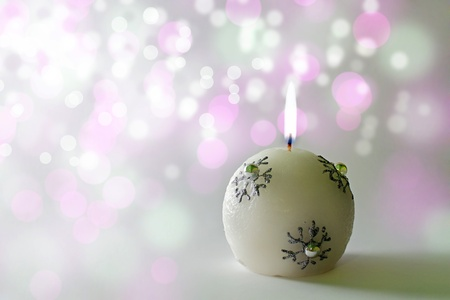 Christmas card, tit christmas candle on a colorful bokeh background photo
