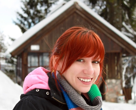 holiday spending: Happy young woman smiling, spending her winter holiday in a mountain cabin Stock Photo