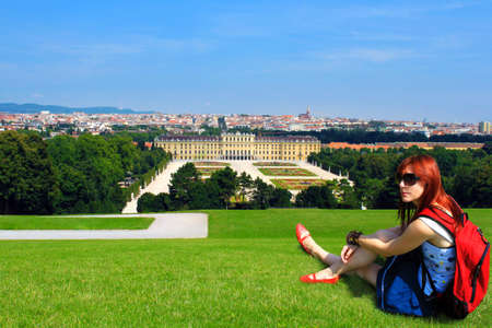 Young woman tourist with backpack, sitting on a lawn on a hill overlooking the beautiful Shoenbrunn castle in Vienna, Austria, backpacking through Europe  photo