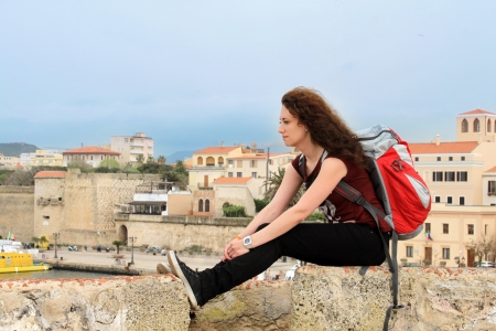 Young female tourist relaxing with her backpack with city of Alghero in the background, Sardinia, Italy photo