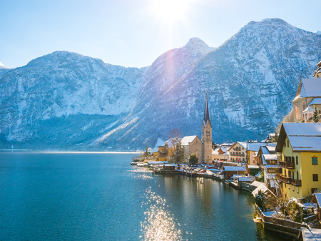 Classic postcard view of famous Hallstatt lakeside town in the Alps moutain ship on a beautiful cold sunny day with blue sky and clouds in winter, Salzkammergut region, Austria Stock Photo