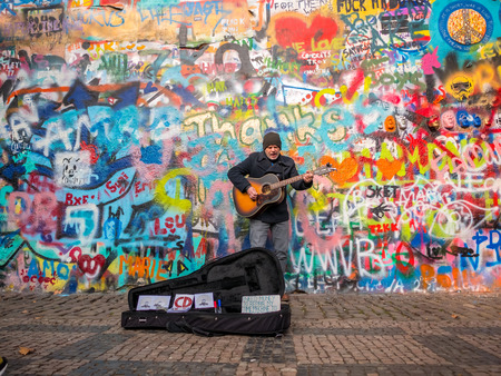PRAGUE, CZECH REPUBLIC - FEBUARY 20, 2018: Street Busker performing Beatles songs in front of John Lennon Wall on Kampa Island.Old town near Charles Bridge.The Historical wall in Europe.