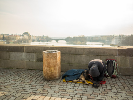 PRAGUE, CZECH REPUBLIC - FEBRUARY 20, 2018: Kneeling man and his dog begging on the Charles Bridge.Destination for traveler around the world. Éditoriale