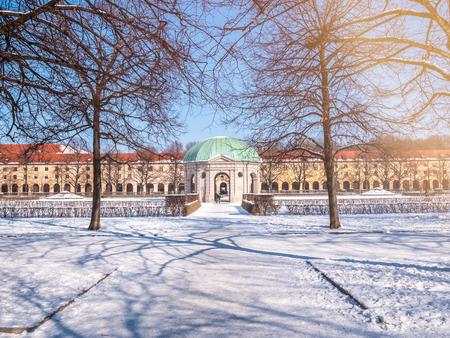 München, Deutschland, Winteransicht mit Schnee des runden Pavillons des Hofgartens im Barockgarten. Sonnentagsbeleuchtung flackern blauen Himmel.