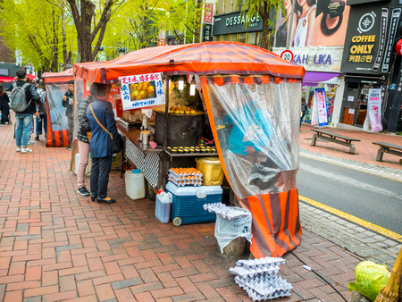 Seoul, South Korea - April 14, 2018: People buying food at a street food stall in Hongdae street on April 14th, 2018 . This area is a famous shopping area for locals and tourists
