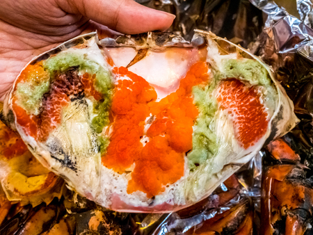 Boiled crab fresh and hot - delicious appetizer Steamed crabs and crab's spawn on aluminium foil Thai seafood, steamed crab showing the delicious crab's eggs inside its shell. Stock Photo
