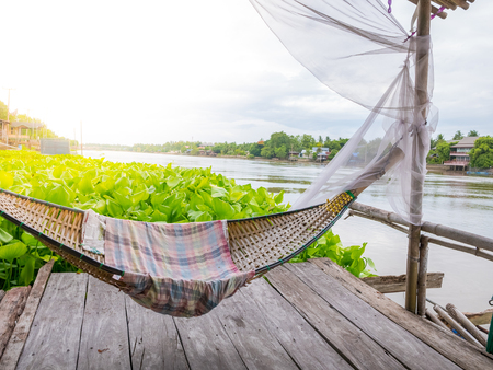 Traditonal thai cuture cradle hanging on the raft at the river water hyacinth.Relax time in the holiday sunnyday. Stock Photo