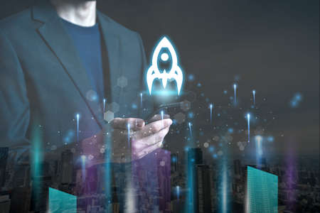 Startup concept with businessman holding tablet or smartphone transparent rocket in launching with network connection on modern virtual interface.