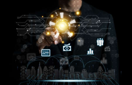 Businessman pointing smart city communication connect technology concept.nternet of things (IoT) technology integrated to manage city asset n dark backdrop.