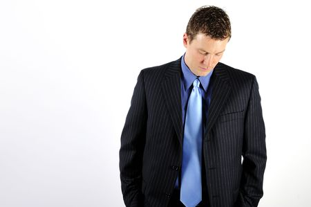 midlife: A young man is wearing a business suit with a blue tie, and is looking down at the floor.  Horizontally framed shot.