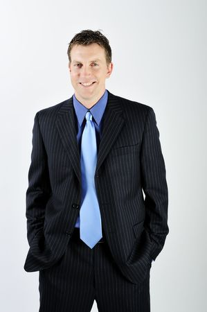 A young man is wearing a suit and a blue tie.  He is smiling at the camera.  Vertically framed shot.