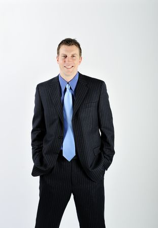 A young man is wearing a suit and a blue tie.  He is smiling at the camera.  Vertically framed shot. photo