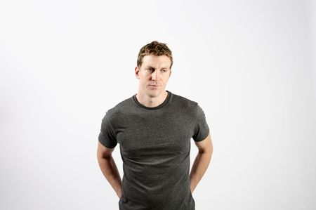 midlife: A young man is standing in a room.  He is looking away from the camera.  Horizontally framed shot.