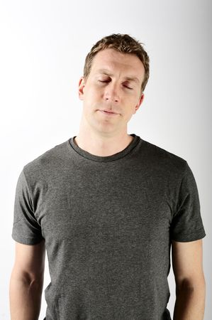 A man is standing in a room with his eyes closed.  He is looking tired.  Vertically framed shot. photo