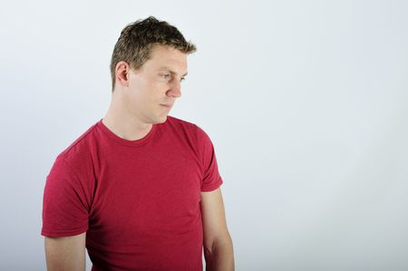 A young man is standing in a room.  He is looking away from the camera.  Horizontally framed shot. photo