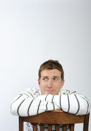 A young man is sitting backwards on a chair and looking away from the camera.  Vertically framed shot. photo