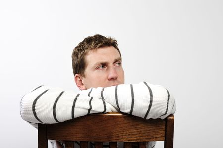 A young man is sitting backwards on a chair and looking away from the camera.  Horizontally framed shot. photo