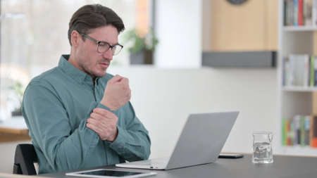 Middle Aged Man having Wrist Pain while working on Laptop