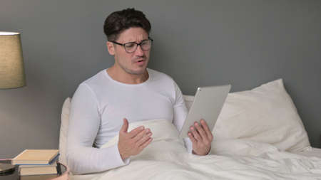 Middle Aged Man Reacting to Loss on Tablet in Bed
