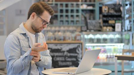 Creative Man having Wrist Pain while Working on Laptop Stok Fotoğraf