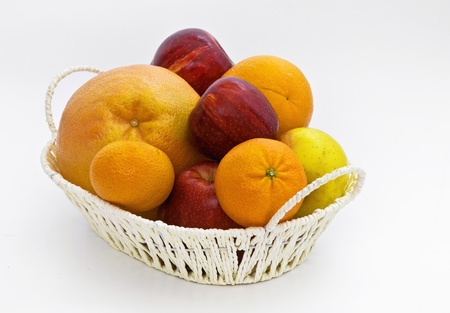 Apples, persimmons and orange fruits in a basket isolated on a white background  photo