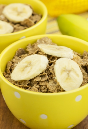 a bowl of healthy bran cereal and a banana Imagens