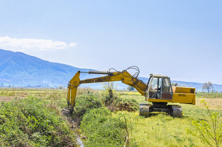 road scraper: track-type loader excavator machine doing earth moving work at green field Stock Photo
