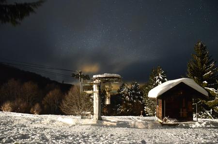 Winter ski slope house on dark star sky and snow photo