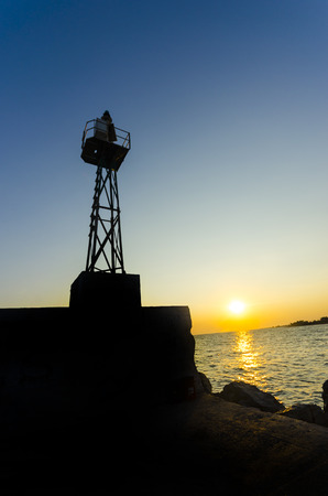 sea port lighthouse tower silhouette with lookout and sunset sky sun horizon photo