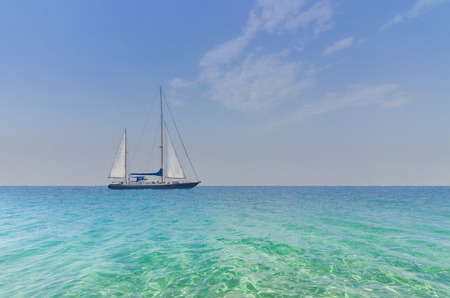 crystal clear: Seascape with sailboat the background of the blue sky.Beautiful sailboat sailing sail blue Mediterranean sea ocean horizon. Crystal clear water and summer sky