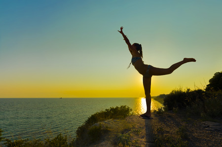 balance beam: Silhouette of Joy. Silhouette of a gymnast backlit girl in balance on a beam at sunset against sea horizon