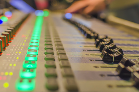 music production: Blurred Hand on a mixer, operating the leader. Night concert scene. Wide angle, shallow deept of field Stock Photo