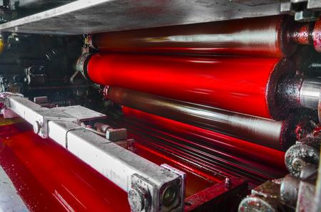 estampado: máquina de impresión, tambor de color magenda roja, luz dramática