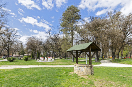 medow: A brick water well with a wooden roof and bucket attached to a rope next to it in a spring colorful park, wide angle Stock Photo