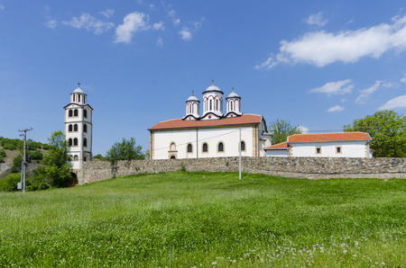 catolic: old church in the mountain landscape and green grass meadow