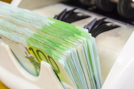legal tender: Euro (EUR) banknotes of 100 on money counter machine - legal tender of the European Union Stock Photo