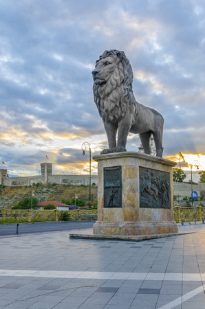 statutes: Lion monument with ancient old citadel fortification  fortress on sunrice bright colors cloudy sky in Skopje, Macedonia