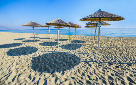 Straw umbrellas on empty seaside beach in caribbean tropical beach and shadow pattern formation photo