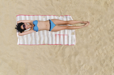 Bermuda Sunbathing, Beautiful brunette girl is sunbathing on an empty beach, aerial view from top  photo