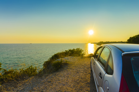Driving into the sunset, Driving sportcar and rear view mirror into the sunset with the countryside sea water hosizon rolling by on a summer day. concept for business, speed or success