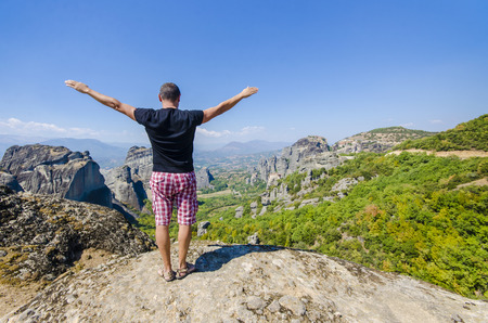 panoramatic: man holds his hands wide open on the top of meteora hill with view of monastery complex, Greece