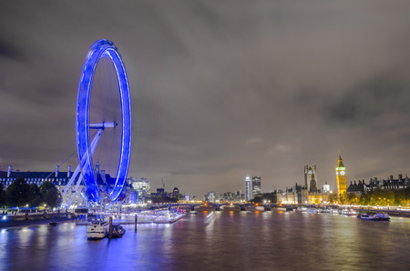 LONDON, UNITED KINGDOM - NOVEMBER 23, 2013   Boats passing along Thames river with night London skyline of Eye, Big Ben, House of Parlament over Westminiister bridge in November 23, 2013 in London, UK, middle angle shoot, long expositure