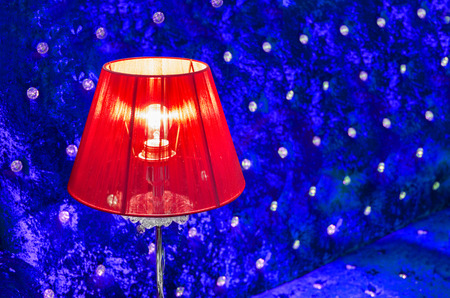 modern vibrant red table lamp and contrast blue sofa background photo