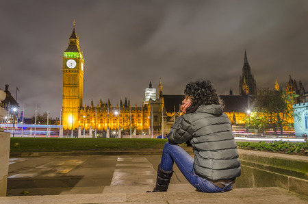beautiful girl takes rest looking at amazing big ben and house of parlament view, London, UK photo